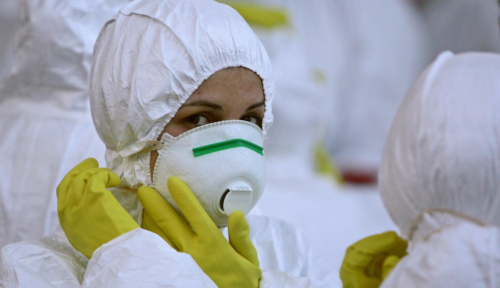 A sanitary worker arranges her mask inside a quarantined area in Bucharest May 21, 2006. Laboratory tests confirmed the presence of birds infected with avian flu in the Romanian capital for the first time since it was detected in poultry in the Danube delta last October, officials said on Sunday. Romania has reported more than 20 bird flu outbreaks over the past week, mostly in the central county of Brasov, just a month after the strain was said to have been eradicated in the Black Sea state.   REUTERS/Bogdan Cristel - RTR1DM1R