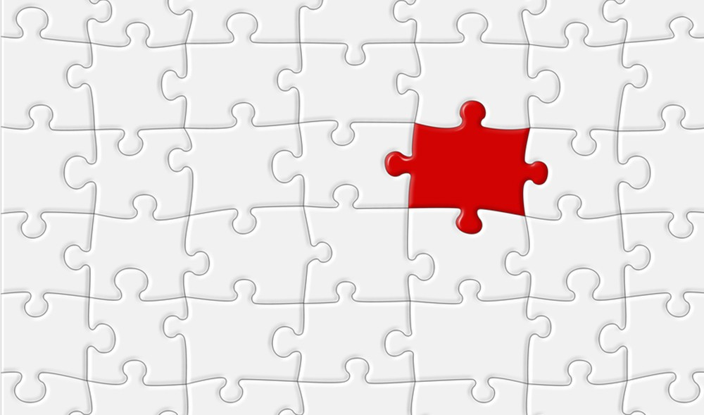 Red jigsaw puzzle piece fitting in to white jigsaw puzzle