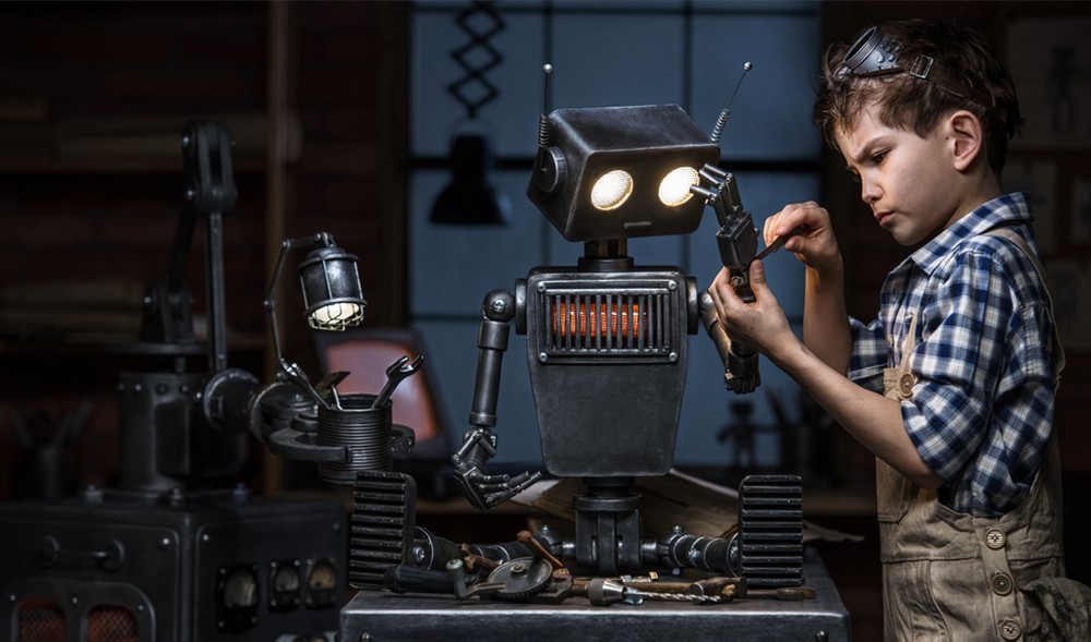 Little boy in a workshop fixing a robot