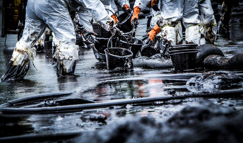 An oil spill being cleaned by individuals with buckets