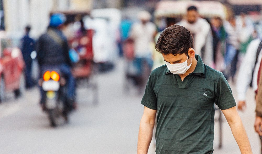 A man walking with a mask over his mouth with a busy city in the background